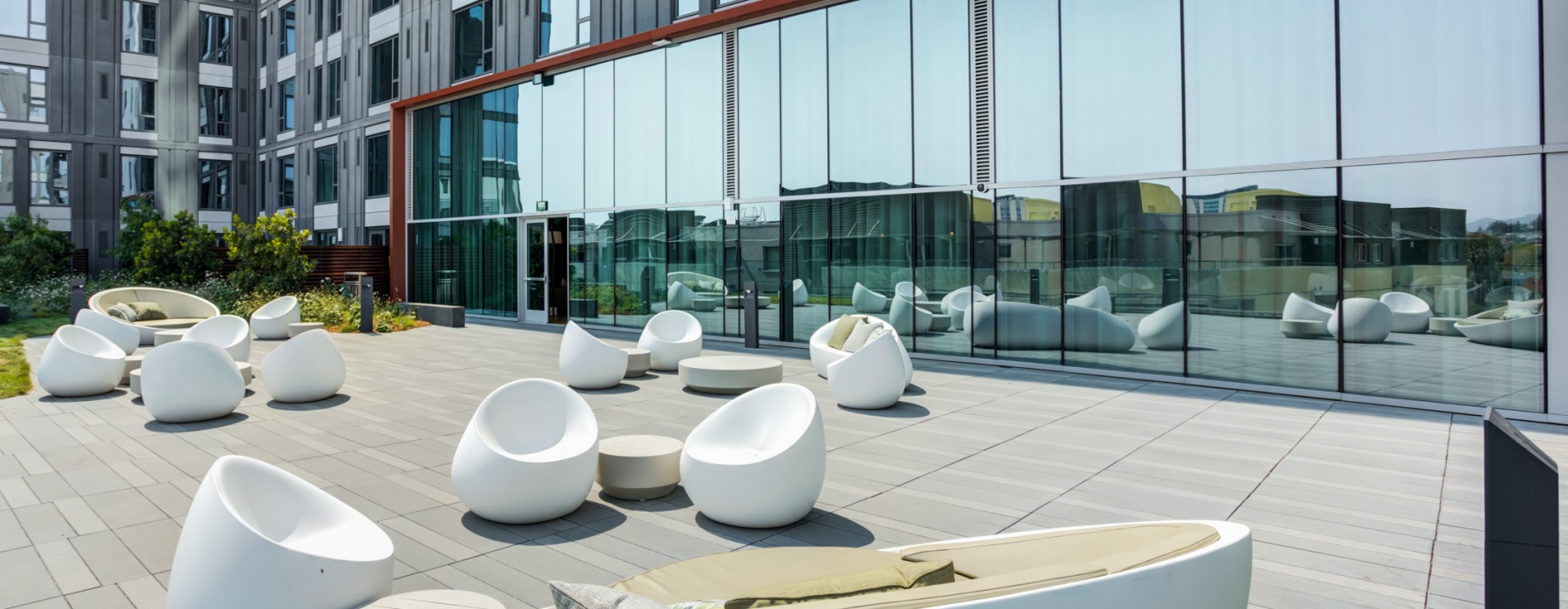 white modern-styled seating with cement floors and landscaping.