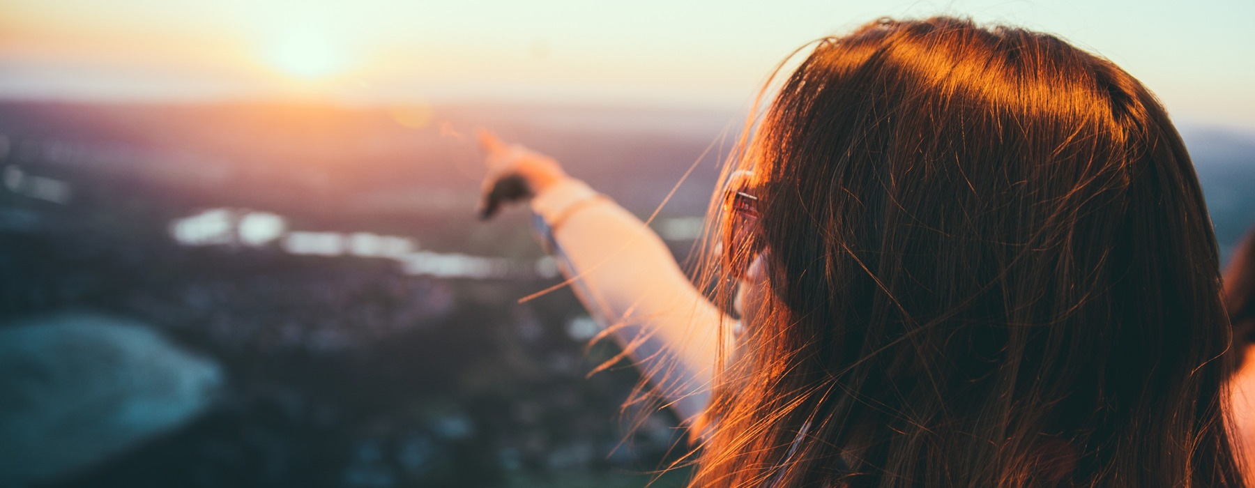 lifestyle photo of woman with sunglasses overlooking rivers and town while pointing toward the sunset